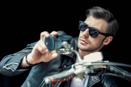 Photo pour Beau jeune homme élégant en lunettes de soleil et veste en cuir assis sur la moto et regardant loin - image libre de droit