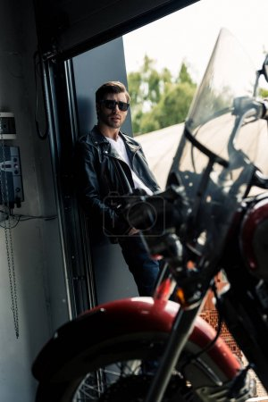 Photo for Stylish young man in sunglasses and leather jacket standing in the garage door and looking at camera - Royalty Free Image