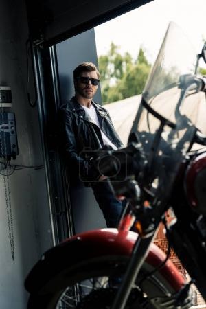 Photo pour Élégant jeune homme à lunettes de soleil et veste en cuir debout dans la porte du garage et regardant la caméra - image libre de droit
