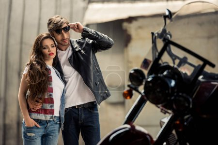 Photo for Stylish young couple standing embracing and looking at motorbike - Royalty Free Image
