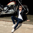 Handsome stylish young man in leather jacket and s...