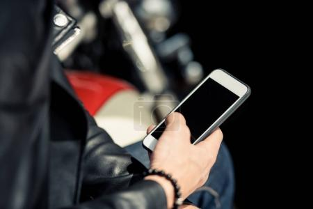 Photo for Close-up partial view of man in leather jacket using smartphone with blank screen - Royalty Free Image