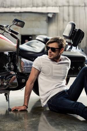 Photo pour Beau jeune homme élégant avec des lunettes de soleil assis près de la moto et regardant loin - image libre de droit