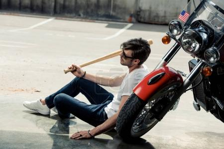 Photo for Handsome young man in sunglasses holding baseball bat while sitting near motorcycle - Royalty Free Image