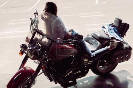 Jeune femme assise sur la moto