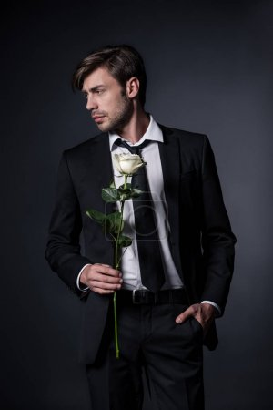 Photo for Man in formal wear holding white rose and looking away isolated on black - Royalty Free Image
