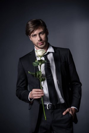 man in suit holding white rose
