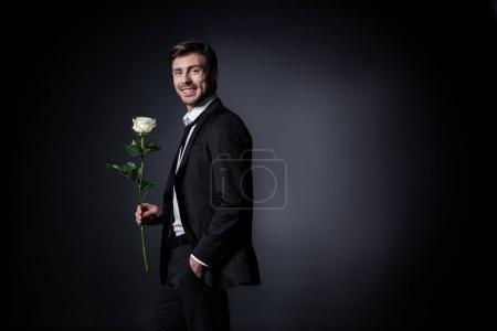 Photo for Smiling man in formal wear holding white rose isolated on black - Royalty Free Image