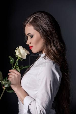 woman smelling rose with eyes closed