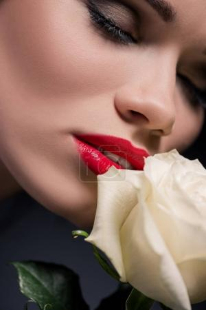lady smelling rose with eyes closed
