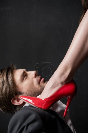 girl stepping on man with red stiletto