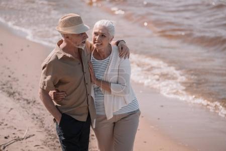 Photo for Happy senior couple walking embracing on sandy beach - Royalty Free Image