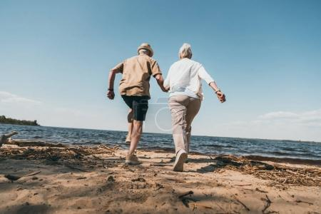 Photo for Back view of senior couple holding hands and running on sandy beach - Royalty Free Image