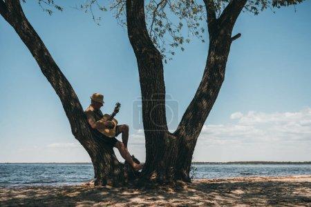 Photo pour Senior homme au chapeau se penchant au grand arbre et jouer de la guitare à riverside - image libre de droit