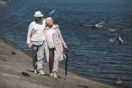 Photo for Happy senior couple walking embracing at quay and looking at flying birds - Royalty Free Image