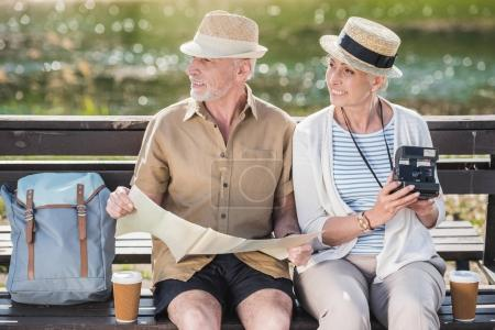 Photo for Happy senior couple of travelers sitting together on bench and holding map and instant camera - Royalty Free Image