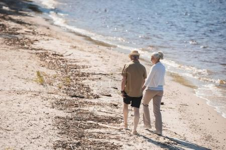 Photo for Back view of senior couple holding hands and walking on sand at riverside - Royalty Free Image