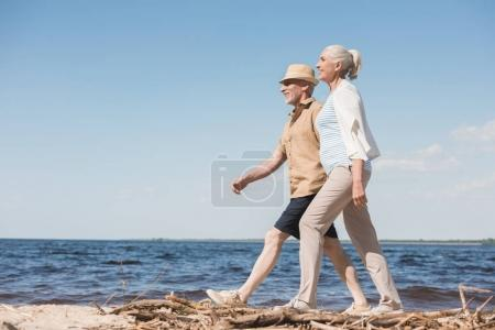 Photo for Side view of happy senior couple holding hands and walking on sandy beach - Royalty Free Image