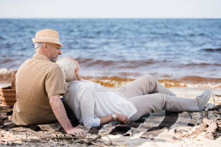 Photo for Beautiful senior couple sitting together on plaid at sandy beach - Royalty Free Image