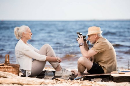 Photo for Side view of senior man in hat photographing smiling woman with instant camera at beach - Royalty Free Image