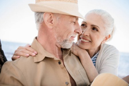 Photo for Close-up portrait of beautiful senior couple embracing and smiling each other outdoors - Royalty Free Image
