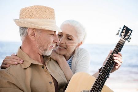 Photo pour Heureuse femme senior étreindre barbu homme au chapeau, jouer de la guitare à l'extérieur - image libre de droit