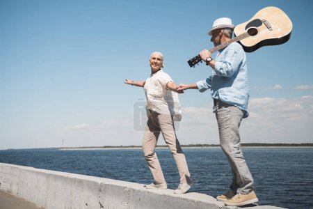 Photo for Happy senior couple with guitar holding hands and walking at quay - Royalty Free Image