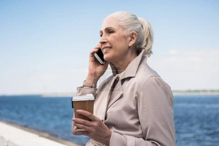 Photo for Smiling senior woman holding disposable coffee cup and talking on smartphone - Royalty Free Image