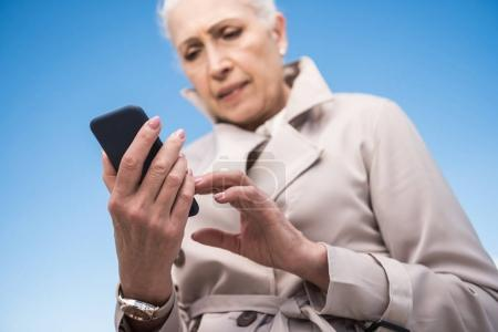 grey haired woman using smartphone