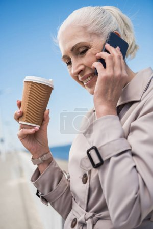 grey haired woman talking on smartphone