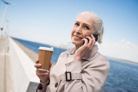 elderly woman talking on smartphone at quay