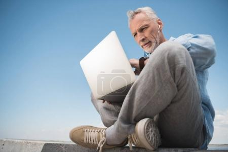 elderly man working on laptop outdoors