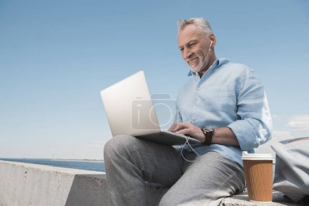 grey haired man typing on laptop