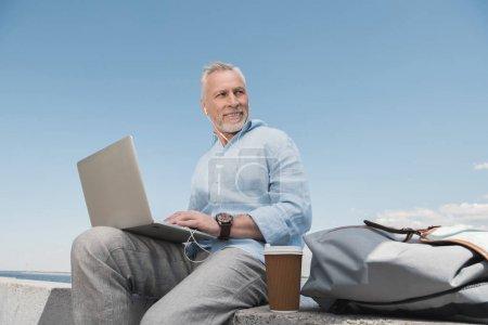 senior man using laptop at quay