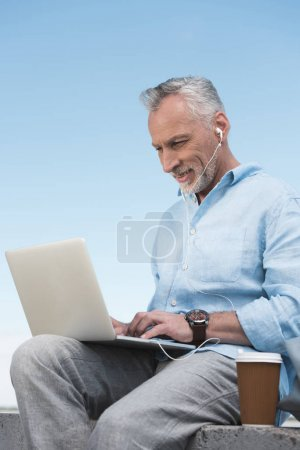 smiling senior man typing on laptop