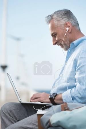 senior man working on laptop outdoors
