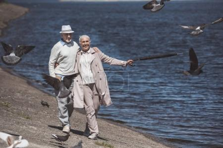 elderly couple walking on river shore