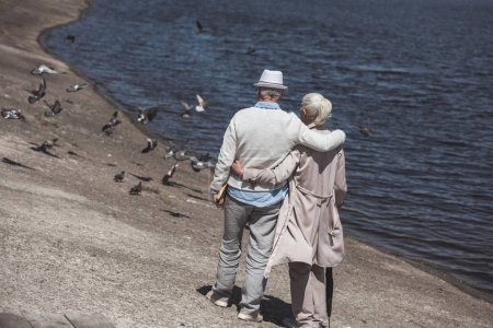 Senior couple walking on river shore