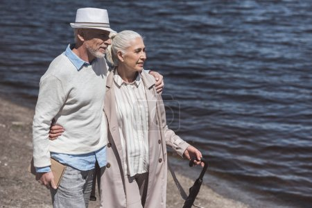 grey haired couple walking on riverside