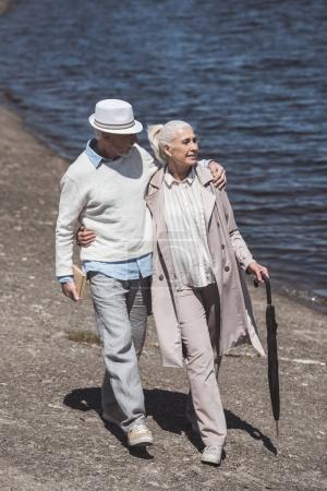 Senior couple walking on river shore