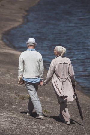 Elderly couple walking on river shore