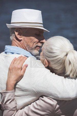 Photo pour Portrait de couple de personnes âgées occasionnels embrassant et capable de baiser dans la journée - image libre de droit