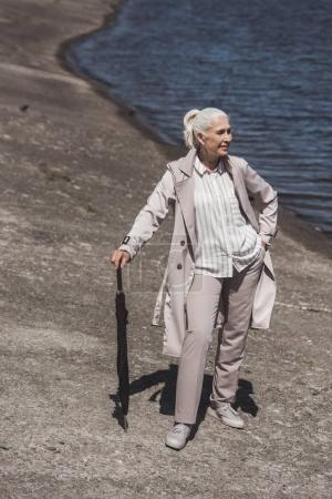 senior woman posing with umbrella on riverside