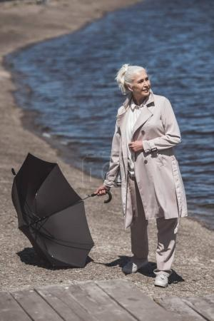 senior woman posing with umbrella on riverside