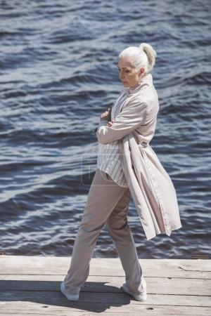 Casual elderly woman posing on riverside