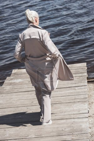 Elderly woman in coat walking at riverside