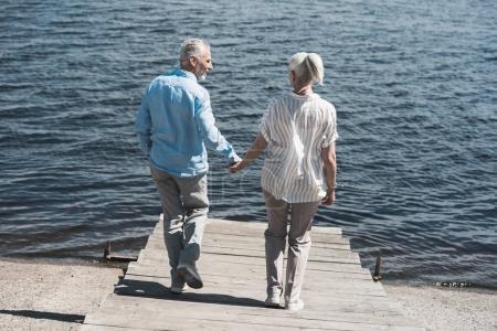 Casual elderly couple walking on riverside