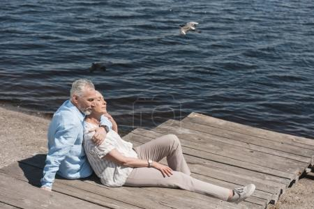 casual elderly couple relaxing at riverside