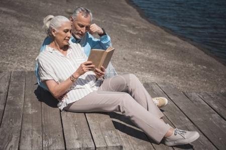 Elderly couple reading book on quay