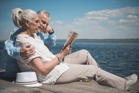 Photo for Elderly couple reading book while sitting on the quay at daytime - Royalty Free Image